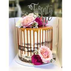 Twenty first cake with caramel drip, fresh flowers and cake topper