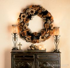 This elegant autumnal look features black and gold deco mesh, printed burlap ribbon—and a surprise appearance by a sassy, black feather boa. Two kinds of oversized flowers round out the design.