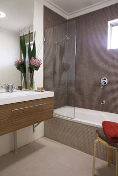 The Colourful Suburban House by Twinkle & Whistle - Bathroom: wall hung vanity, mosaic tiles, glass partition, native flowers
