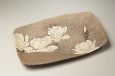Low cloth-impressed rectangular platter decorated with blooming white hibiscus flowers, ca. 1988-1990 Stoneware with brown, white, rust under-glazes and gold, green, burgundy over-glazes 1 x 10 1/4 x 15 3/8 inches Inv# 7214 $ 2,800 Image