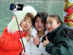 These Chinese girls aboard an excursion boat on West Lake at Hangzhou, China, are intent on taking a selfie.