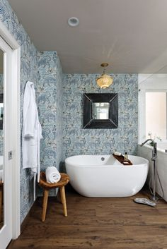 A tiger motif wallpaper and vintage light fixture adds a unique edge to this spa-like retreat.