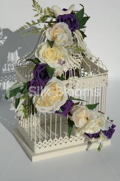 http://www.silkblooms.co.uk/images/table/martina_purple__ivory_rose_birdcage_centerpieces.jpg