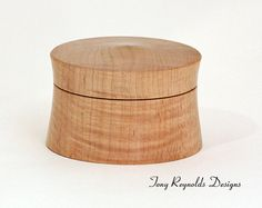 Turned Curly Maple Keepsake box. Perfect for storing that special little something. This one is made from beautiful Curly Maple. It measures 4.125 in diameter by 2.75 tall.    As with all our boxes, they are turned with end-grain orientation so it will hold its round shape. The lid and the base are made from the same piece of wood so are grain matched. The lid fits with a slight suction fit, but can vary slightly depending on the humidity. The finish is buffed lacquer.    The box in the…