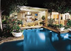 This swimming pool and patio features a gourmet outdoor kitchen complete with an outdoor TV for guests to enjoy as they stop by the swim-up bar adjoining the outdoor kitchen area. Mark Scott Associates http://www.luxurypools.com/blog/entryid/90/poolside-living-patio-designs-ideas.aspx