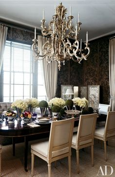 The centerpiece of a Manhattan dining room designed by Stephen Sills is a Louis XVI table and chairs lit by an Italian silvered chandelier. Displayed on the table are antique silver beakers from Dienst + Dotter.