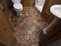 This bathroom floor features 60 square feet of solid White Oak and Birch tree rounds and twigs. The floor is job-site finished, using a matte wax finish.  > Love this timber tree round flooring idea. > Not for the bathroom though!