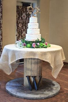 Rustic wedding cake on a wooden wire spool with a burlap cover & whitetail deer antler cake topper.