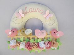 Mais uma opção para decorar a porta de maternidade... Uma guirlanda com passarinhos no jardim florido! <br> <br>Confeccionado num círculo de feltro, com enchimento. O nome do bebê é bordado. <br> <br>Pode ser feito nas cores de sua preferência!