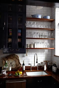 Kitchen : West Village Apartment | Daily Dream Decor. Subway tile with dark grout. Open wood shelving. Dark cabinets. Glasses displayed on small kitchen open shelving.