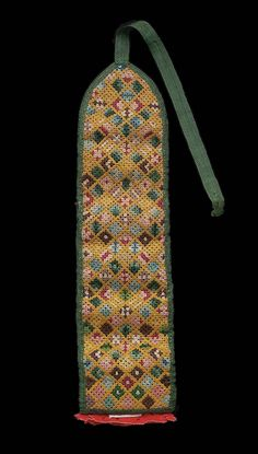 A sewing case, long and narrow in shape, designed to be rolled up and tied, outside embroidered with polychrome silks in rococo stitch, design of assorted small squares, inside a series of brocade pockets designed to contain sewing equipment, at bottom a needle book of five leaves of red wool with pinked edges and cut out design, edges bound with green silk tape, tie of sametape.