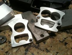 "Fresh out of the waterjet. 'The Face Opener' returns accompanied by the brand new 'Minion.' (My kids see a resemblance to the little yellow guys from 'Despicable Me.' These are UC dusters/bottle openers in 1/4"" thick 6061 aluminum. These still need etching, tumbling and wire brushing to be finished. Should be up on my site and Bladeforums this week. Cheers Y'all!  -Overmountain Knife and Tool."