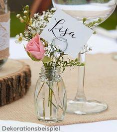 Kleine Glasvasen im Vintage-Stil werden zu blumengeschmückten Platzkartenhaltern zur Vintage- oder Boho-Hochzeit: An den kleinen Gläschen wird eine Drahtschlaufe befestigt und die mit den Namen der Gäste versehenen Kärtchen werden eingesteckt. Inhalt: 4 Stück mit Haltern und weißen Karten. Größe: ca. 3,5 cm Durchmes...