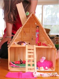 A sweet doll house that's made entirely out of popsicle sticks.