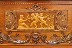 An art cased, Schiedmayer upright piano with a Baroque style case. Cabinet features ornately carved cherubs and scrolls around a central frieze. Corinthian fluted pillars with acanthus leaves frame the cheeks. Ornate brass hinges with a scrolling design.
