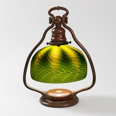 """This is not contemporary - image from a gallery of vintage and/or antique objects. """"Favrile"""" Tiffany Lamp  A Tiffany Studios New York Favrile glass and bronze desk lamp, featuring a green """"Damascene"""" shade with iridescent decoration suspended from within a decorated """"Harp"""" base in a china red patina."""