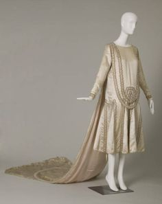 Dress, wedding-style, of off white satin with strands of pearl bead rosettes and silver-colored thread trim. Long sleeves; below-the-knee length. Long attached train with edge embroidered in a scallop pattern, Lanvin, 1925