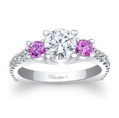 Simply stunning and so unique, this diamond engagement ring features a cathedral shank with a prong set round diamond center, flanked on the sides with pink sapphires.  The shoulders are graced with shared prong set diamonds running down the ridge of the euro shank for a sophisticated modern look that rides well on the finger.<br />  <br />  Also available in yellow, rose gold, 18k and Platinum.