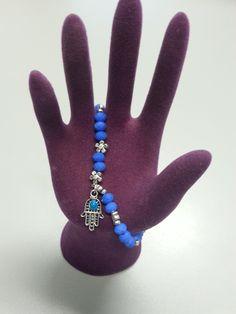 Maravillosa pulsera azul cielo con piedras y una mano de Fátima plateada con una bola del mismo color. Increíble para todo tipo de ropa vaquera o de cualquier color