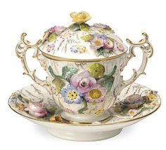 AN ENGLISH PORCELAIN FLOWER ENCRUSTED TWO-HANDLED CHOCOLATE CUP, COVER AND STAND AND A SIMILAR SINGLE-HANDLED CUP AND COVER,<br />THE FIRST UNDERGLAZE BLUE PAINTED 'CD' FOR COALBROOKDALE, CIRCA 1820, THE SECOND 19TH CENTURY, POSSIBLY COALBROOKDALE,<br />the similar of smaller size <br />The cup, cover and saucer 6in. (15cm.) high (5)<br />