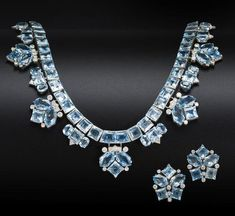 An aquamarine and diamond necklace and earring suite, by Cartier, circa 1950 The articulated row of square-cut aquamarines suspending alternating trios and chevrons of vari-cut aquamarines and brilliant-cut diamonds, to a foxtail-link backchain, together with a pair of earclips en suite, diamonds approximately 2.10 carats total, signed Cartier, necklace numbered.