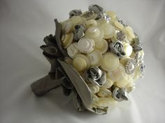 a lovely high end vintage reproduction brooch is the main feature in the centre of the bouquet. There are also the sweetest little clusters of faux pearls and crystals.  The petals, and handle are silver silk dupion, the ruffle is double layered with silk dupion and vintage look striped ribbon.  A bouquet of heirloom quality bouquet, perfect for a elegant vintage themed wedding or destination wedding, (you can carry it in your hand luggage).