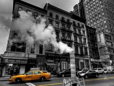 """This is a street scene in Lower Manhattan with a color isolation done on the yellow from the taxi and stripes on the road. The steam coming out of the manhole """"chimney"""" comes from the New York City steam system. This system carries steam from steam generating stations under the streets throughout the city to heat, cool and supply power to the high-rise buildings."""