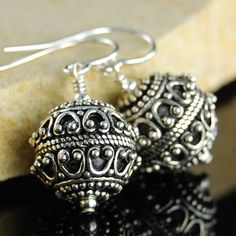 Bali style earrings featuring round textured dangle with an antiqued blackened finish. These light weight beads dangle freely form sterling silver earwires. Bead size: 11.5mm Total length: 1 1/8 inche