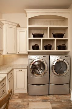 Love the way this laundry room is setup with the front load washer and dryer. The storage above the machines is great along with the folding counter.
