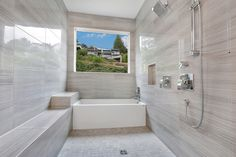 This walk in tub and shower feature a Maax Slide in Tub and Pfister plumbing faucets. Tiled walls and bench are Forms Polished Porcelain Bianco Veined in 12X24 with a mud pan in the a 2X2 version. #greatnwhomes #billjohnsonphotography @pfisterfaucets @maaxinc