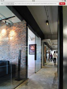 Combinación cristal y tabique con piso concreto aparente