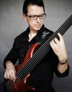 """Alain Caron on gorgeous mahogany fretless bass. Research - cSw - http://www.pinterest.com/claxtonw/4-5-6-strings/ - Expert luthier George Furlanetto (of F Bass in Hamilton, Ontario) has built basses for Caron for 20 years. He worked together with Caron to develop the """"F Bass Alain Caron model"""" (AC6), which has the tone of a solidbody fretless yet has the dynamic characteristics of an acoustic guitar."""