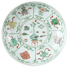 Large coupe peinte dans les émaux de la famille verte en porcelaine de Chine de la Compagnie des Indes d'époque Kangxi Grande coupe en porcelaine peinte dans les émaux de la famille verte, décoré au centre d'un vase fleuri et des attributs du lettré, l'aile décorée dans des réserves des huit emblèmes bouddhiques (ba ji xiang). Au revers marque au double cerclage et à la feuille d'armoise.