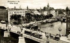 Die Ansichtskarte zeigt die Grüne Brücke über den Alten Pregel in Königsberg. Sie war die Verbindung von der aus südlicher Richtung kommenden Vorstädtischen Langgasse zur Kneiphöfischen Langgasse und weiter zur Krämerbrücke über den Neuen Pregel. Heute werden beide Pregelarme einschließlich der Kneiphof-Insel von einer modernen Hochbrücke überspannt. Am rechten Bildrand kann man die Köttelbrücke erkennen. Ansichtskarte ca. 1912.