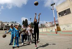 """Palestinian girls play basketball during a training session as part of a sports program launched by the """"Palestinian Association for Children's Encouragement of Sports"""" (PACES) on August 21, 2013, in Gaza City. PACES was founded in 2006 with the central aim of providing healthy, structured after-school sports programs for Palestinian girls and boys. MOHAMMED ABED/AFP/Getty Images"""