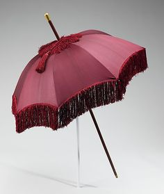 Parasols were often carried in the manner of a walking stick and this is an example of a style which was made to actually function as a walking stick, with a metal tip at the base of the handle, and a knob on top. Another interesting feature is the leather-covered shank, handle, and spike rather than the typical wood.
