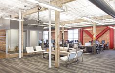 An open ceiling and the original brick walls and wood beams exposed around the perimeter creates a unique environment for technology firm Airware's office space.