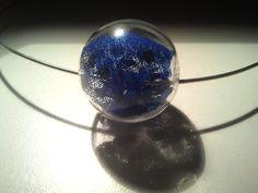 """Girocollo """"BLUE FUN """" formato da elemento circolare in metallo con chiusura a  scomparsa e boule in vetro soffiato  che all'interno racchiude  frammenti di prezioso tessuto tempestato di piccole paillettes  blu elettrico. Quando le paillettes vengono colpite dalla luce rimandano particolari bagliori. Possibilità di orecchini coordinati."""