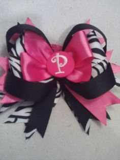 Hot pink, black/white zebra strip, black, and initial center