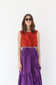 Centered knot for a sculptural addition to the crisp silhouette. Buttoned back closure & sleeveless. Perfect for layering with a high-waisted summer skirt or a pair of distressed Boyfriend or Mom jeans. By Rachel Comey