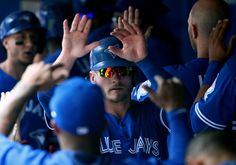 Josh Donaldson Photos Photos - Josh Donaldson #20 of the Toronto Blue Jays is congratulated by teammates in the dugout after scoring a run in the fourth inning during MLB game action against the Cleveland Indians on July 3, 2016 at Rogers Centre in Toronto, Ontario, Canada. - Cleveland Indians v Toronto Blue Jays