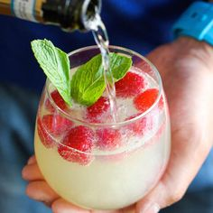 """It only takes five minutes to make this """"damn delicious"""" cocktail, so if you're in crunch time, whip out some prosecco, limoncello and pour over frozen raspberries and mint sprigs. (Get the full recipe from Damn Delicious)"""