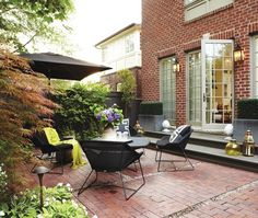 Marilyn Denis's Backyard ~ French doors provide a classic entrance onto this small patio. Tumbled red brick is inset with strips of gravel to add interest to the yard's patio. Layering accessories on the steps draws eyes up to the home and onto the deck. A low table does double duty for lounging and dining, instead of trying to squeeze in a dining table.