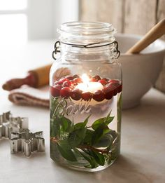 Cast a warm glow on long winter evenings. Place a branch of greenery at the bottom of a glass jar or vase. Fill the jar about two-thirds full with water. Drop in cranberries and a floating candle. Its soft, flickering flame will add ambience to your dinner-party table.