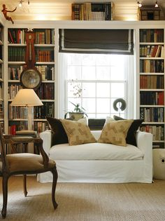 Take cheap bookcases, line them next to each other, and trim out the tops. Looks like built-ins