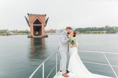 Bride and groom portrait on a Lake Superior Yacht, in front of the iconic Marquette Lower Harbor Ore Dock. If you look closely, you'll see that it was pouring rain when these photos were taken!