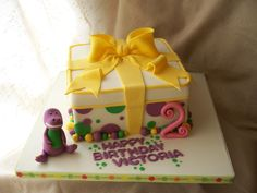 https://flic.kr/p/6obs7P | Barney gift box inspired cake with figure | Vanilla cake with a hint of almond filled with fresh strawberries and whipped cream and crumbcoated in vanilla buttercream. I made this cake for a friends daughter's 2nd birthday, she loves Barney!! Barney is made from fondant, first time that fondant could stand up to the figure molding test!! It was made with a free sample I got from the cake competition....not bad!