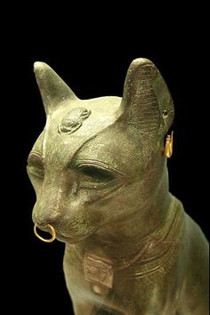 A late period bronze cat in the form of the goddess Bastet. Jewelry is ancient but not necessarily original to this piece.