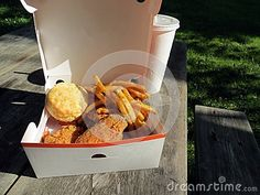 Boxed meal of spicy fried chicken, French fries, and a biscuit on a picnic table in the park.