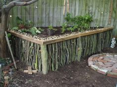 Raised garden bed mad of sticks.  credit: jamieicecream on Instructables [http://www.instructables.com/id/Natural-Wood-Raised-Garden/]